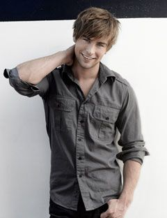 chace crawford in gray button down rubbing neck and smiling