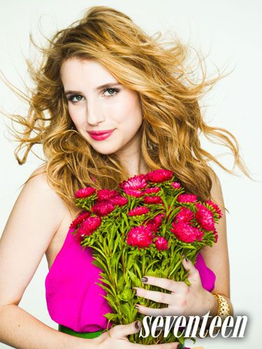 Emma Roberts in a light purple top holding magenta flowers for May 2011 issue