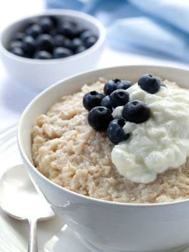 oatmeal with cream and blueberries on top in a bowl