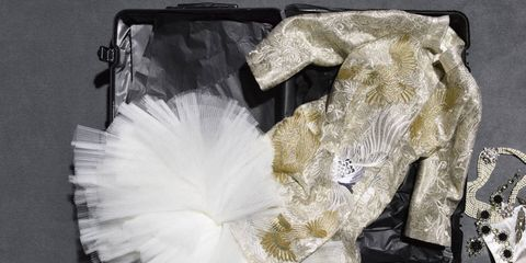 The jewels could be wrapped in satin, the brocade evening coat could be hung with care, but the tulle crinoline posed an almost insurmountable challenge.Marchesa brocade evening coat and slip dress with crinoline ($6,995). Rimowa suitcase (here and throughout, from $750); Chanel pearl necklace ($5,800); Prada necklace ($1,925); Stephen Russell earrings (price on request).