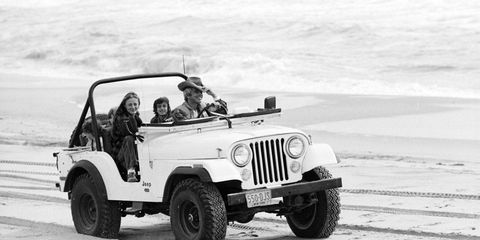 Ralph Lauren and Ricky Lauren driving on the beach in East Hampton with their children in November 1977.