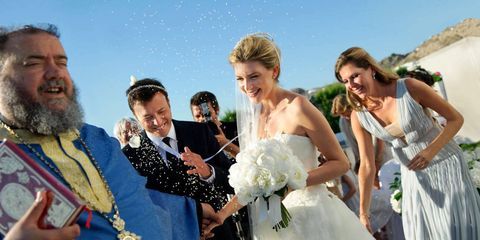 With their crowns tied together, Phoebe and Nicolas take their first steps as husband and wife with her sister Vasi and Father Pappas Petros close by.