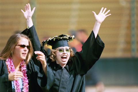 Former First Child Chelsea Clinton (R) throwing her arms up in celebration at beginning of graduation ceremony at Stanford University.  (Photo by Chuck Nacke/The LIFE Images Collection/Getty Images)