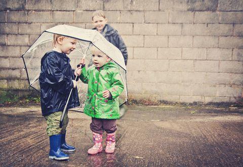 Trousers, Outerwear, Jacket, People in nature, Umbrella, Raincoat, Hood, Walking shoe, Precipitation, Boot,