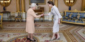Actress Angelina Jolie is presented with the Insignia of an Honorary Dame Grand Cross of the Most Distinguished Order of St Michael and St George by Queen Elizabeth II in the 1844 Room on October 10, 2014 at Buckingham Palace, London. Jolie is receiving an honorary damehood (DCMG) for services to UK foreign policy and the campaign to end war zone sexual violence. (Photo by Anthony Devlin - WPA Pool/Getty Images)