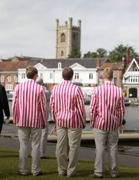 <p>Rowers in their traditional club blazers watch the boats come down the course.</p>