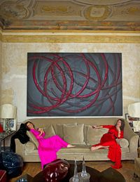 <strong>Visconti</strong> (left) and her daughter <strong>Madina</strong> in matching <strong>Bottega Veneta</strong> gowns, curl up on the living room sofa beneath an enormous painting by <strong>Aaron Young</strong>.
