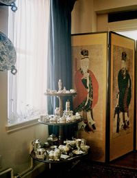 A chinoiserie screen behind her collection of silver.