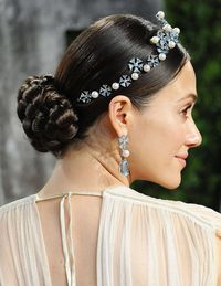 "Inspired by Grace Kelly on her wedding day, Emmy Rossum's tiara-topped braided chignon imparts a polished elegance. Rick Gradone, the hairstylist behind the showstopping 'do, explained how to pull off a crown in the twenty-first century: ""The sleekness of this look keeps it more elegant and contemporary, whereas softer and fuller styles make tiaras look more prom queen or pageant-like. The look has to be as clean and kempt as possible."" Gradone also recommended following the shape of the headpiece for maximum impact. ""Since this Chopard tiara was angled into a v, I drew a middle part that directly paralleled its peak and allowed me to sculpt the hair into a similar silhouette,"" he said. ""Then I crafted the braid at the nape of the neck so that the end of the tiara met right at the middle of the bun, which gives the eye a nice line to follow."""