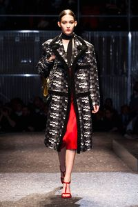 The range of coats was tremendous, bringing in the nostalgic riffs Prada loves—over-sized toppers done in graphic black-and-white prints with a sophisticated Sixties psychedelia feel. These were played against silky loose dresses in bright red or rich purple.
