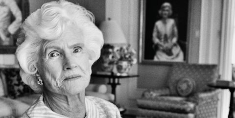 """Roberta McCain, in her living room near portraits of herself and of her father-in-law, Admiral John S. """"Slew"""" McCain Sr. The latter was painted by Thomas E. Stephens in 1943."""