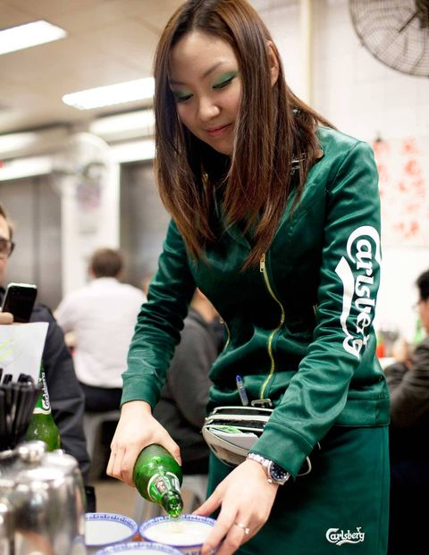A beer girl at Tung Po pours Carlsberg into bowls.