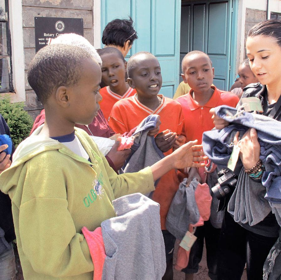 Emmanuelle Chriqui distributes clothing donations to orphans.