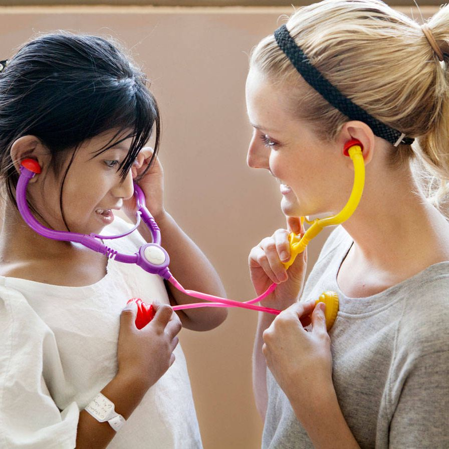 Lydia Hearst, an Operation Smile ambassador, shows a patient how a stethoscope works.