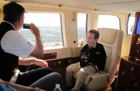 PGA Golfer Bo Van Pelt snaps a photo en route to Homestead Speedway in Donald Trump's helicopter as his son, Trace, looks on.