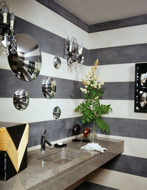 Alternating stripes of gray and white paint enliven the powder room of a modernist home in Geneva, which was decorated by Alexandra de Garidel-­Thoron of the Swiss design studio Thébaïde. A constellation of convex mirrors appears to float above the stone sink.via elledecor.com