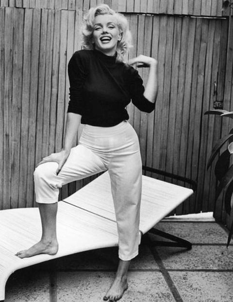 When you picture Marilyn Monroe, it's likely you envision her baring skin in a dripping sequin gown. However, when the blonde bombshell wasn't illuminating the screen or painting the town red, she was cozied up in classic American staples. Most often you could find Monroe in a fitted turtle neck or low-cut blouse, paired with a neutral pair of trousers and loafers. The key to keeping her basic look refined was the tailoring on each of the pieces, as they accentuated her famous curves.