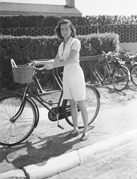 Jeanne Murray Vanderbilt pauses with her bicycle by the entrance of the Southampton Bathing Corporation, Southampton, New York, late 1940s.