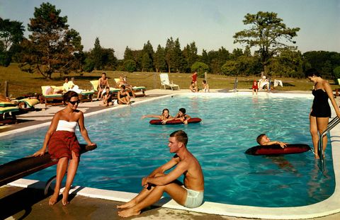 Guests lounging at the outdoor swimming pool at the Tocker Mill Inn, Southampton, New York, 1960.