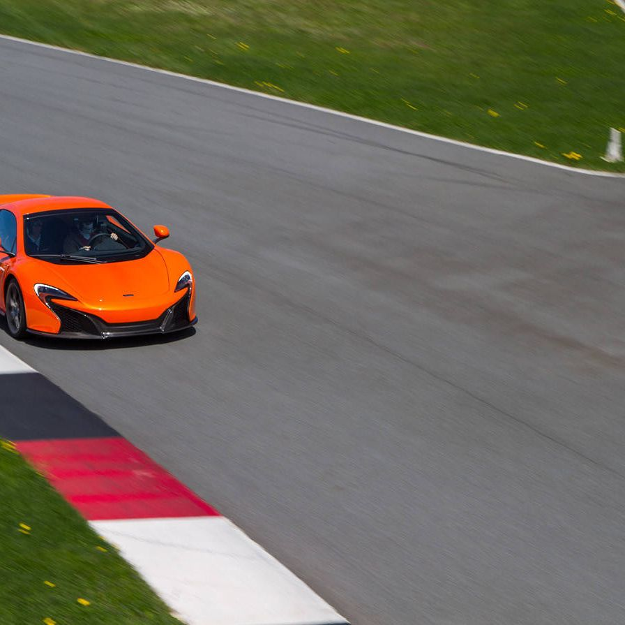 """Driving a family sedan on the expressway can't compare to driving a high-performance sports car on a racetrack any more than using the Nordic Track at Planet Fitness compares to playing in the NBA. So when McLaren Automotive, the automotive engineers behind 12 Formula 1 racing championships, invited a slew of marginally qualified gearheads to test their latest creation—the McLaren 650S, named after its 641-horsepower engine—they were wise to provide a team of racers with Grand Am experience to demonstrate proper form.Before strapping the press into racing helmets for some high-speed reporting, introductions were made. The 650S comes in some new colors—Mantis Green, Aurora Blue, and the arrestingly unsubtle Tarocco Orange named after the Italian variety of blood orange—and the latest marque provides some improvements over its already speedy predecessors, the 12C and the P1. The upgrades come mostly in added horsepower, and improved aerodynamics and downforce, and something called """"inertia push"""" that puts a little hurry-up in the gear changes. Because customers missed certain aspects of the race-car roar in this car's immediate predecessors, McLaren has added a purely theatrical flourish that it has dubbed """"cylinder cut"""": a distinctive throaty rumble in the exhaust every time you shift up in sport mode. My racing tutor, Greg Liefooghe, a driver for BimmerWorld racing, very nonchalantly took the 650S through its paces at the Monticello Motor Club, a 650-acre racing preserve with a sinuous 4.1 mile racetrack about two hours north of New York City. Although customer surveys suggest that McLaren clients actually put their cars to regular use, Monticello is the sort of club that McLaren imagines its customers will join for the occasional adrenaline rush: members can race there in private at track speeds or join in on race days with other supercar owners. The car costs about $265,000 in its stripped down version, but once all the options are added ($11,000 here for the carb"""