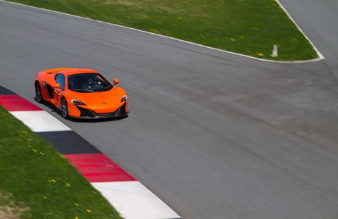 "Driving a family sedan on the expressway can't compare to driving a high-performance sports car on a racetrack any more than using the Nordic Track at Planet Fitness compares to playing in the NBA. So when McLaren Automotive, the automotive engineers behind 12 Formula 1 racing championships, invited a slew of marginally qualified gearheads to test their latest creation—the McLaren 650S, named after its 641-horsepower engine—they were wise to provide a team of racers with Grand Am experience to demonstrate proper form.Before strapping the press into racing helmets for some high-speed reporting, introductions were made. The 650S comes in some new colors—Mantis Green, Aurora Blue, and the arrestingly unsubtle Tarocco Orange named after the Italian variety of blood orange—and the latest marque provides some improvements over its already speedy predecessors, the 12C and the P1. The upgrades come mostly in added horsepower, and improved aerodynamics and downforce, and something called ""inertia push"" that puts a little hurry-up in the gear changes. Because customers missed certain aspects of the race-car roar in this car's immediate predecessors, McLaren has added a purely theatrical flourish that it has dubbed ""cylinder cut"": a distinctive throaty rumble in the exhaust every time you shift up in sport mode. My racing tutor, Greg Liefooghe, a driver for BimmerWorld racing, very nonchalantly took the 650S through its paces at the Monticello Motor Club, a 650-acre racing preserve with a sinuous 4.1 mile racetrack about two hours north of New York City. Although customer surveys suggest that McLaren clients actually put their cars to regular use, Monticello is the sort of club that McLaren imagines its customers will join for the occasional adrenaline rush: members can race there in private at track speeds or join in on race days with other supercar owners. The car costs about $265,000 in its stripped down version, but once all the options are added ($11,000 here for the carbon fibre exterior upgrade, $6900 there for the racing seats, and so on) most deliveries top out in the mid $300,000 range.What's the biggest difference driving a 650S through winding country roads and then trying it flat out on the track? Well, sure, on a closed course you can hit top speeds without fear of imprisonment. (I have no idea how fast I actually drove the thing because it was way too fast to look down to check.) But one maneuver you'd never try to pull out on a public road is to brake with such aggression. When it was my turn to drive—with the experienced Formula 1 driver in the passenger seat to talk me through the chicanes and sharp corners and double apex curves—the real surprise was how fast the McLaren could shed the speed, from full stomp to almost nothing in what felt like a few yards, so you could take a curve with remarkable suddenness, from flat out to flat out in the opposite direction in one quick shake. Brake like that in the Minivan at home and the entire family would be somersaulting through the neighbors' pachysandra."
