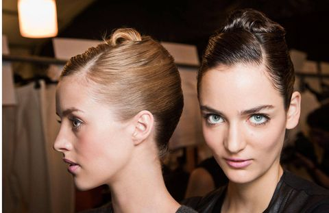 At Carolina Herrera, hair stylist Orlando Pita created a sleek seashell-esque double French twist, setting the style with By Byron's Spirulina Hair Spray.