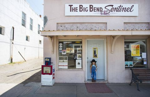 "Just months after printing its first issue, in 1926, the Big Bend Sentinel consolidated with an older paper, one whose name presaged its hometown's unlikely second life: Marfa New Era.After World War II, the decade-long ""Drought of Record"" dried up the land, and much of the town's social life with it. Giant was filmed here in 1955; years passed without further incident. Then, in 1972, came art world-weary minimalist sculptor Donald Judd, who (with the Dia Foundation footing the bill) bought half the town, becoming its biggest employer.Unsurprisingly, then, the Sentinel is flanked by Judd holdings, and its stark interior is furnished in the master's style. A framed topographic map of Texas is at once handy reference and objet d'art. On the front page, culture shares column inches with immigration and the drug war, along with whatever celebrity gossip falls into the paper's lap.A young reader with a fresh copy of The Big Bend Sentinel."