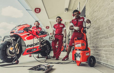 Team mechanics tend to racer Andrea Dovizioso's Ducati GP13 at the Circuit of the Americas course in April.
