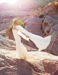Monique Lhuillier gown and cape&#x3B; Philip Treacy Limited headpiece&#x3B; Demner cuff: Ippolita bangles.