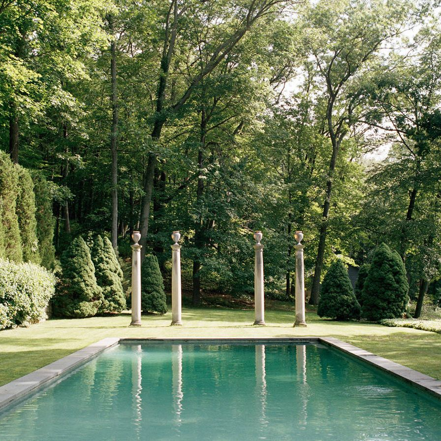 The American limestone columns were found at Michael Trapp in West Cornwall, Connecticut, and provide the visual focal point at the edge of the swimming pool. The lounge chairs are from Brown Jordan.