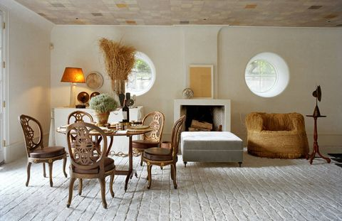 The guesthouse's hand-painted ceiling is by Peruvian-born artist Patricia Arnillas, and the Canadian marble used for the floor is from Bedford Stone. Two shades of tinted plaster were applied to the walls. Amid favorite objects, including a rice straw chair by Kim Hyun-been and an early Philippe Hiquily sculpture atop an 18th-century Dutch table stand, is an ottoman upholstered in silk velvet from Holland & Sherry.