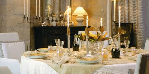 A candlelit table draped in layers including a trapunto-like Marseilles bedcover.