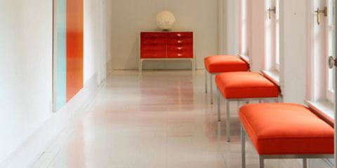 Perry's affinity for minimal no-fuss design is clear in this modernist hallway. Verner Panton chandeliers softly illuminate the orange custom benches and vintage console.