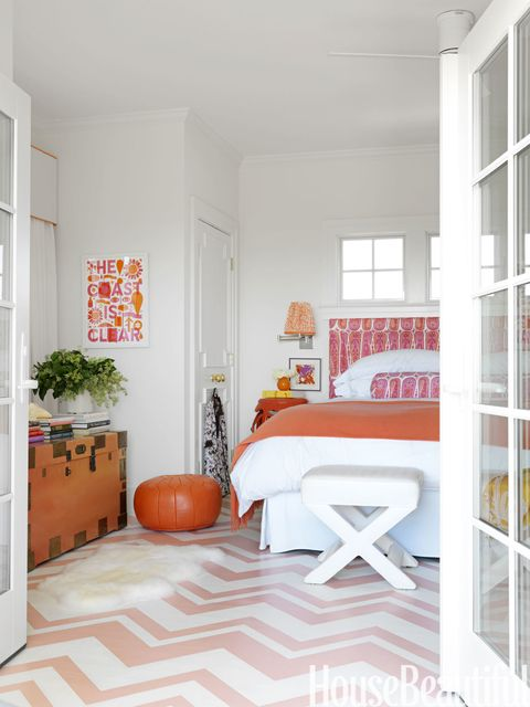 """The master bedroom has a very retro feel to it,"" says Berman, ""with the pink, tangerine, and lavender color palette, the paisley linen, and the zigzag Missoni-esque pattern on the floor."" The floor is painted Salmon Berry and White Dove, both by <a href=""http://www.benjaminmoore.com/"" target=""_blank""> Benjamin Moore</a>. The headboard is upholstered in Henry in Rose by <a href=""http://www.raoultextiles.com/"" target=""_blank"">Raoul Textiles</a>. Pouf from <a href=""http://www.johnderian.com/index_home.html"" target=""_blank""> John Derian</a>."