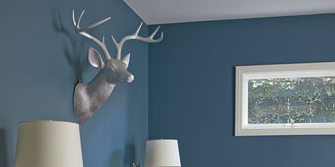 """Big color works in a small space: Benjamin Moore's Newburg Green on the guest room walls plays off fabrics in hot tropical colors. Esquenazi silver-leafed a wooden deer head to give the room a """"sprinkling of out-there embellishment."""""""