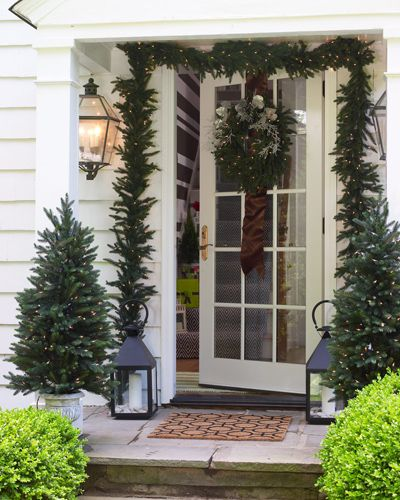 <p>Give guests a healthy dose of holiday cheer from the minute they ring the doorbell. Lush boxwoods, mini-evergreens, and a lush garland peppered with lights turn this entry into an inviting wonderland. Oversized lanterns flank the doorway providing soft light and added shimmer, while ribbon and icicle-like accents enrich the wreath. </p>