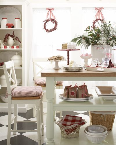 When company calls, pull out the treats. Holiday-hued cake stands and trays are stylish staging areas for baked goods and candies. Keep a stack of bright white plates ready along with napkins and forks. Here, a vintage bread box is repurposed as a container for baby's breath, greens, and berries. Bold, checked linens fill a wire basket. Twig wreaths from the crafts store adorned with faux berries make the frosty window an enticing backdrop.
