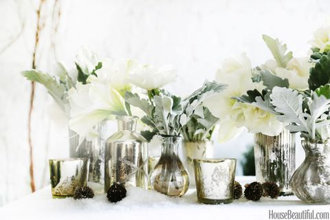 "<p>Think winter white for a glamorous and festive table. ""Simple, clean winter whites and the sparkle of the season"" was the inspiration for this arrangement, which consists of Dusty Miller, spray roses, and amaryllis.</p>"