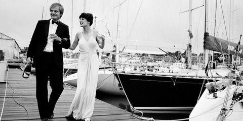 Trousers, Coat, Photograph, Standing, Suit, Monochrome, Dress, Style, Formal wear, Watercraft,