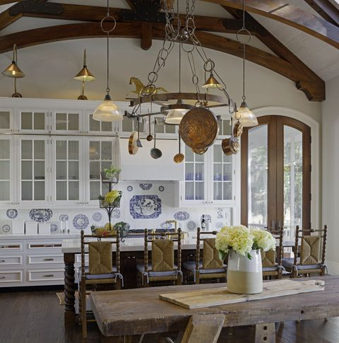 """The pot rack in the kitchen is influenced by a big English manor. I designed it specifically for this family. The beams and trusses came from a barn in Maine. The tile backsplash in the kitchen is a handmade, custom design I had made depicting dogs, horses, and the family."""