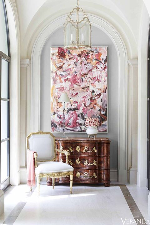 Choice antiques and eye-catching art make a visual statement outside the master bedroom. Chair, Michael Taylor; pendant, Dennis & Leen; lamp, Visual Comfort; 18th-century French chest of drawers.