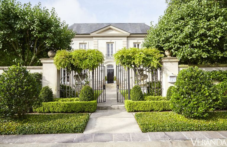 French inspired house of Tara Shaw in New Orleans. Formal hedges flank the entrance to the house.