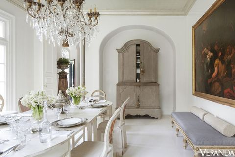 <p>The dining room floors were painted a custom high-gloss color to give the antiques a fresh look. Gustavian buffet à deux corps, 18th-century Swedish bench, and 19th-Century Italian chandelier, Tara Shaw Antiques; table, Tara Shaw Maison; walls in a custom Fine Paints of Europe color.</p>