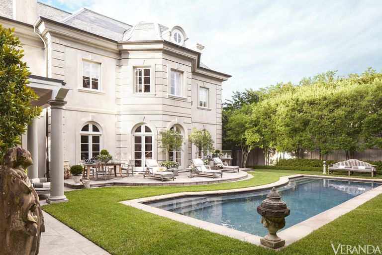 Parisian style house of interior designer Tara Shaw in New Orleans. The flagstone pool surround complements the graceful curves of the terrace. Chaises with cushions in a Sunbrella fabric, bench, and chairs, David Sutherland; 19th-century French urn, Tara Shaw Antiques. </p>
