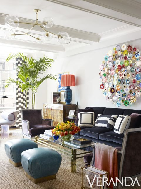 <p>Furnishings with strong shapes and deep colors ground vivacious art in the living room. Custom sofa in a JB Martin fabric; armchairs in a Holland & Sherry fabric, Todd Alexander Romano; vintage Karl Springer ottomans in a Moore & Giles leather; coffee table, John Salibello; chandelier, Lindsey Adelman; rug, Merida; art, Klari Reis. </p>