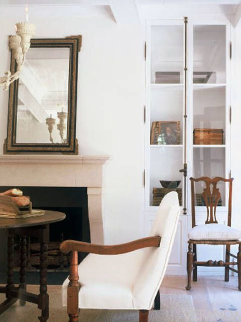 <p><span>The bookshelf cabinetry of this Virginia townhouse has been painted to blend into the walls, and the coffered ceiling, also the same color, adds a subtle architectural element to the space. The exterior doors have been painted black to suggest the different experience you will have outside—and in this case, to mimic the visual elements found in a black fence in the distance.  </span></p>