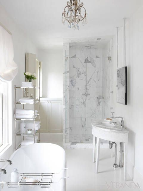 Luxurious white bathroom with marble shower, Gustavian antique console table vanity, mirror hung from ceiling, and freestanding tub. #whitebathroom #bathroomdecor #luxurious #pamelapierce #Gustavian