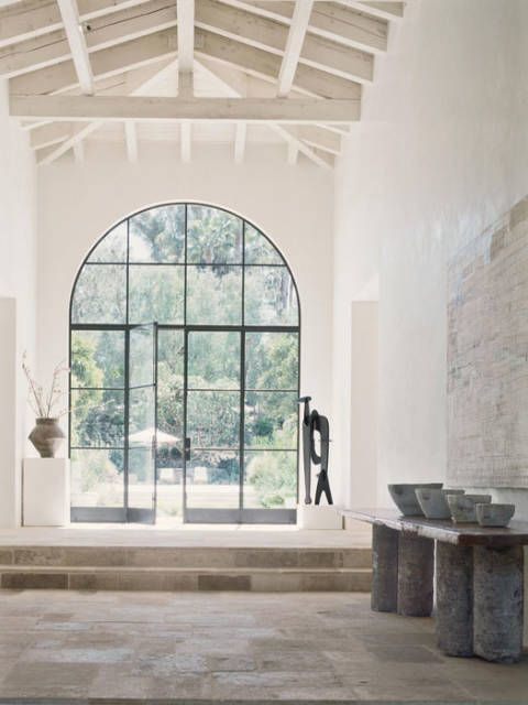 """<a href=""""http://archironworks.com/"""" target=""""_blank"""">Architectural Iron Works</a> doors and windows. Lum'Art lanterns. In entry, Han vase. Isamu Noguchi sculpture. Table with blue stone base and English 17th-century oak top. French 19th-century mortars. Painting by Mark Bradford. French antique limestone flooring by <a href=""""http://www.xsurfaces.com/"""" target=""""_blank"""">Exquisite Surfaces</a>."""