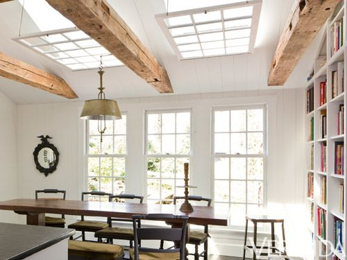 <p>When a homeowner wanted to maintain his sun-drenched kitchen—yet disliked the 1980s-style skylights—Carter sought ways to make them complement the home's original architecture. His solution: hanging mullioned windows from chains under the recesses. They echo the look of the nearby windows, while masking the modern, plate-glass skylights. Plus, suspending them parallel to the floor and beams, they visually level the pitched ceiling, another '80s vestige.</p>