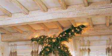 <p>For Charlotte Comer's living room in Dallas, florist Bryan Long decided to take the Christmas decorations to new heights—literally.  Two slim cedars threaded with lights and Venetian glass bells frame the fireplace mantel just below the ceiling's whitewashed beams to dramatic effect.</p>